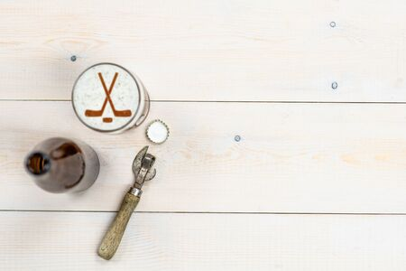 Mug of beer with silhouettes of hockey sticks on beer foam and bottle and retro opener on wooden background. Top view. Empty space for text.