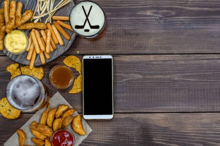 Varied snacks and beer with silhouettes of hockey sticks on beer foam and smartpnone on dark wooden background. Internet delivery concept. Top view. Empty space for text. Фото со стока