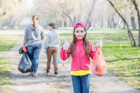 Young girl with garbage bags showing thumbs up. Ecology concept.