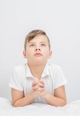 Young boy prayaing at bedroom before bedtime. Looking up. Standard-Bild