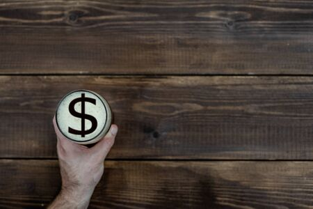 mans hand holds a mug of beer with sign of a  dollar usa  on a beer foam. Top view. Dark wooden background. Empty space for text.