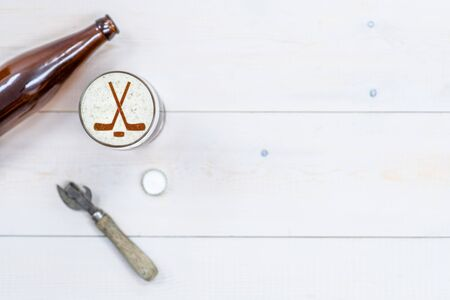 Mug of craft beer with silhouettes of hockey sticks on beer foam with bottle and retro opener on wooden background. Top view. Empty space for text. Stock fotó