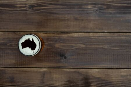 Mug of beer with silhouettes of Australia on foam. Top view. Space for text.