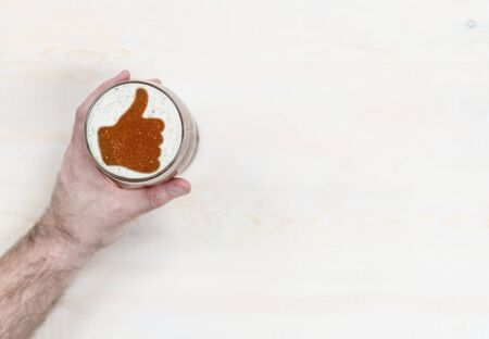 Mans hand holds a mug of beer with silhouettes of a thumbs up gesture. Space for text.