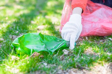 Eco-friendly volunteer with garbage bags  and plastic bottle.