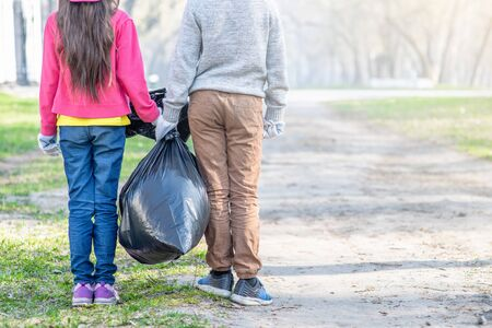 Kids carry a bag of trash. Back view. Ecology concept. Empty space for text. Reklamní fotografie