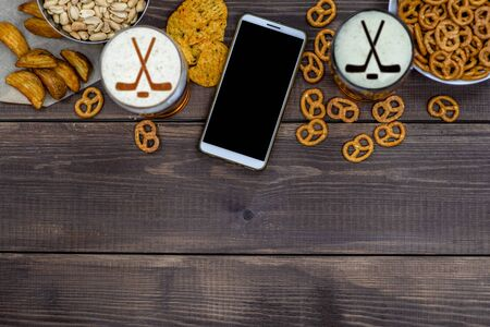 Varied snacks and beer with silhouettes of hockey sticks on beer foam and smartpnone on dark wooden background. Internet delivery concept. Top view. Empty space for text. Reklamní fotografie