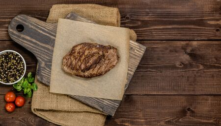 Fresh grilled meat. Grilled beef steak medium rare on wooden cutting board. Top view. Empty space for text.