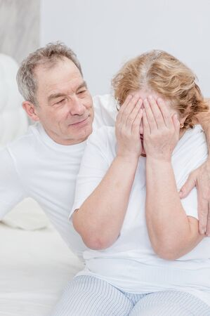 Senior man calms his crying wife at bedroom.