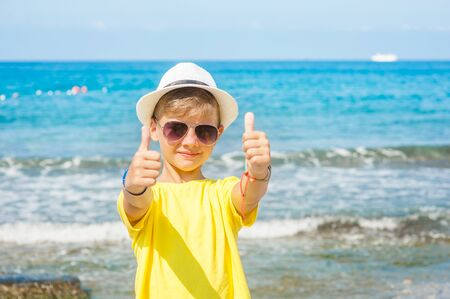 Young boy in a summer hat by the sea showing thumbs up. Empty space for text.