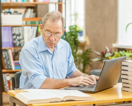 Old man using laptop in library.