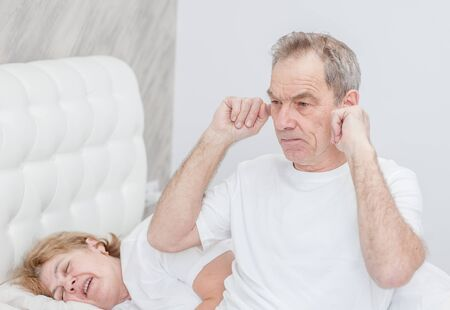 Senior man plugged his ears and can not sleep because his wife snores.