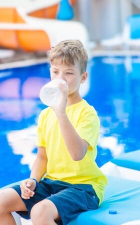 Little boy drinks water from a plastic bottle by the pool.