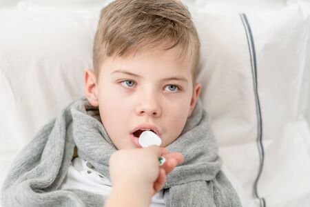 Sick little boy take medication pouring in a spoon. Banque d'images - 133390846