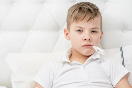 Sick boy with thermometer in his mouth sitting on the bed at home. Empty space for text. Stock Photo