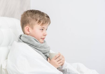 Sick boy with warm scarf sitting on the bed with cup. Empty space for text.