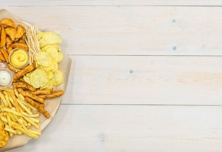 Assorted snacks  on light wooden background. Empty space for text. Top view.