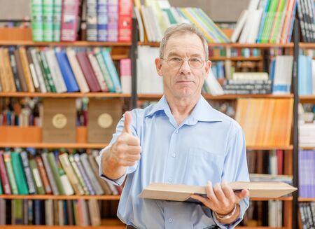 Hombre mayor con libro abierto en la biblioteca mostrando los pulgares para arriba. Espacio vacío para texto. Foto de archivo