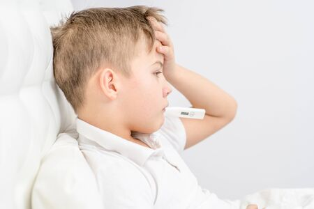 Sick boy with thermometer in his mouth sitting on the bed at home. Banque d'images - 133682941