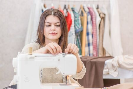 Young woman seamstress sitting and sews on sewing machine. Hobby sewing as a small business concept. Reklamní fotografie