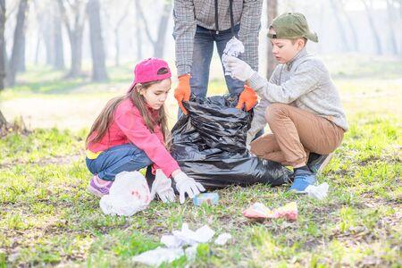 Volunteers picking up trash in the park. Volunteer and ecology concept. Reklamní fotografie