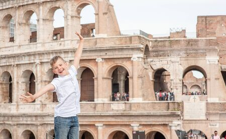 Very happy boy near coliseum in Rome, Italy. Travel concept. Empty space for text.