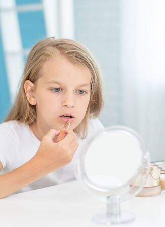 young girl paints lips in front of a mirror at home.