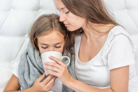 Young mother taking care of sick daughter in bedroom and giving her cup of tea.