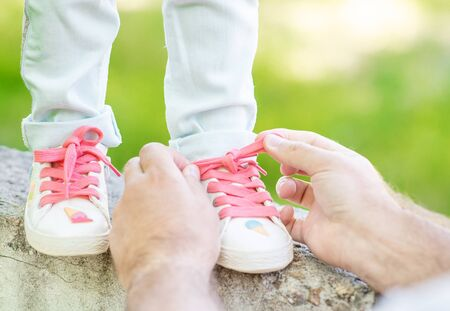 Close up father helping her little daughter to tie shoelaces on summer day.