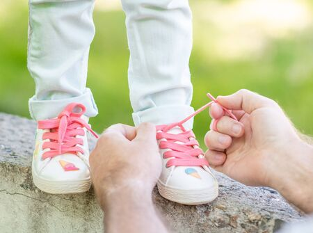 Parent helping his little daughter to tie shoelaces on summer day.