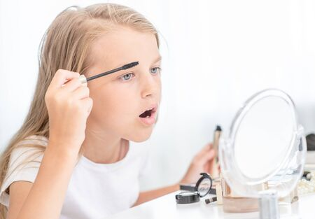 Little girl applies mascara on eyelashes looking mirror at home.
