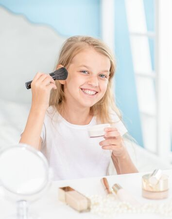 Little girl puts makeup on face at home. Stock fotó