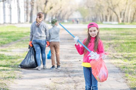 Volunteer girl collects paper trash in the park. Ecology concept.