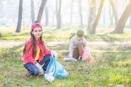 Un groupe d'enfants ramassent des ordures dans le parc. Concept de bénévolat et d'écologie.