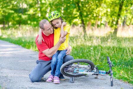 Vater betrachtet die Wunde seiner Tochter, die vom Fahrrad gefallen ist.
