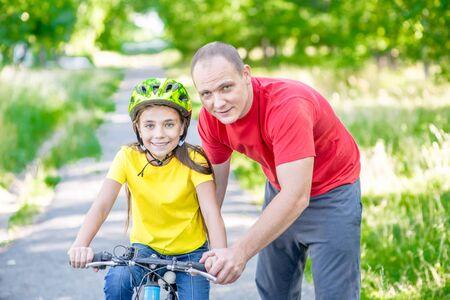 Uśmiechnięty ojciec uczy córkę jeździć na rowerze w parku.