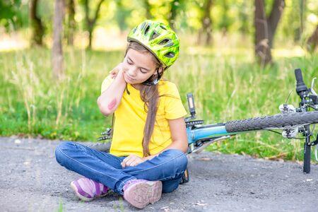 Little girl fell from the bike in the summer park.