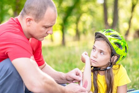 Father puts a bandage on a wound to little girl, who fell off his bicycle.