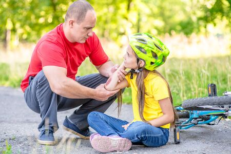 Father looks at the wound of his daughter, who fell from a bicycle.