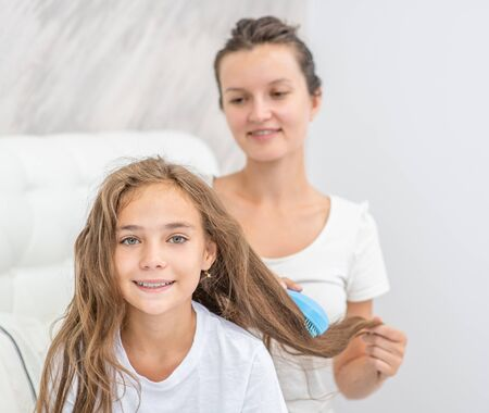 Happy young mom is combing her daughter at home. Stockfoto