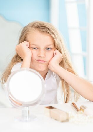 Sad little girl sitting and looking in the mirror at home.