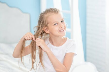 Smiling girl braids herself in the morning at home. Stock fotó