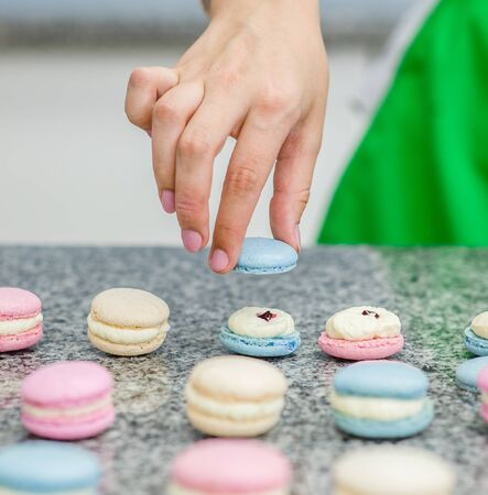 Close up chef decorating macarons shells at confectionery or pastry shop.