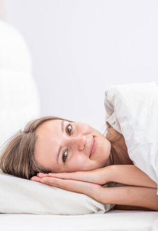 Beautiful smiling young woman lying on the bed at home before bedtime. Reklamní fotografie