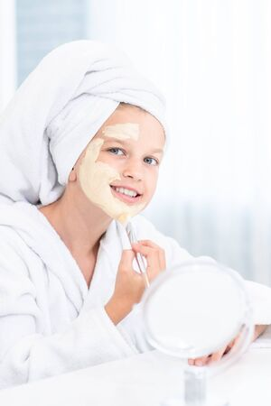 Young girl in towel on her head  make a clay facial mask at home. Stock fotó