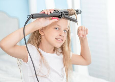 Smiling girl using curling iron at home in morning.