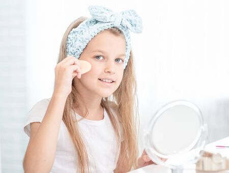 Little girl uses sponge to apply the cream on her face.