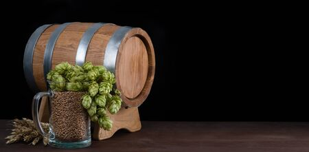 Barrel and beer glass with malt, wheat and fresh green hops like a foam on dark wooden table. Empty space for text. Black background.