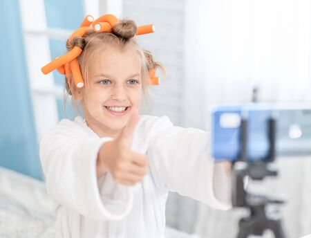 Young girl showing thumbs up, asking online audience to like and subscribe.