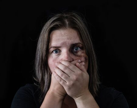 Young beaten up woman looking at camera and covered her mouth with her hands. Isolated on dark background.